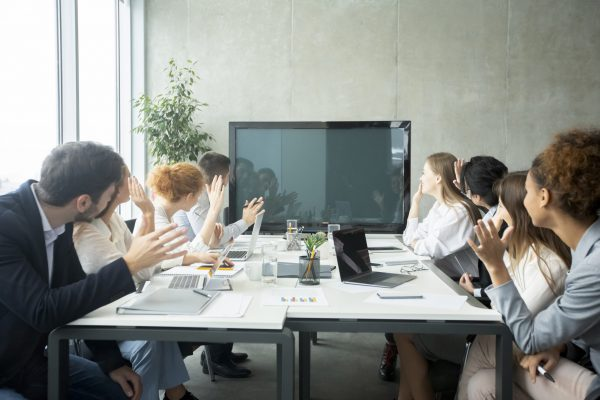 Videoconference. Businesspeople greeting boss, waving hands to tv screen